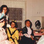 Photo en couleur de cinq femmes dans une cuisine habillées de robes colorées et de chapeaux.