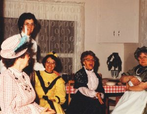 Colour photo of five women wearing colourful dresses and hats in a kitchen.