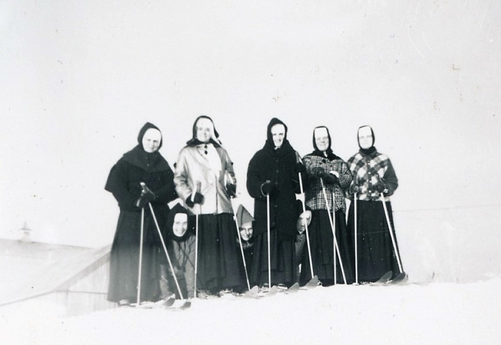 Black and white photo of five women wearing skis and three others kneeling in the snow. They are wearing veils and winter garb.
