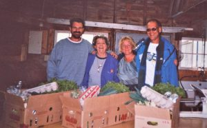 Colour photo of four farm employees receiving baskets filled with fresh vegetables and eggs.