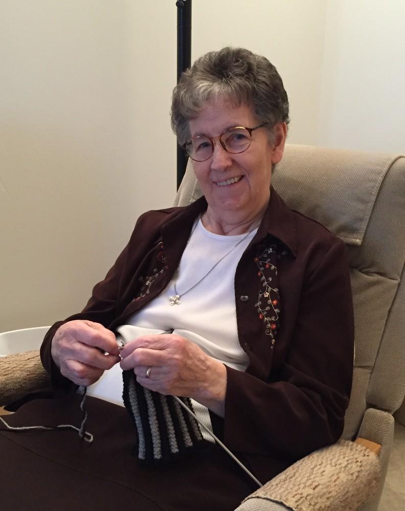 Elderly woman sitting in a rocking chair knitting.