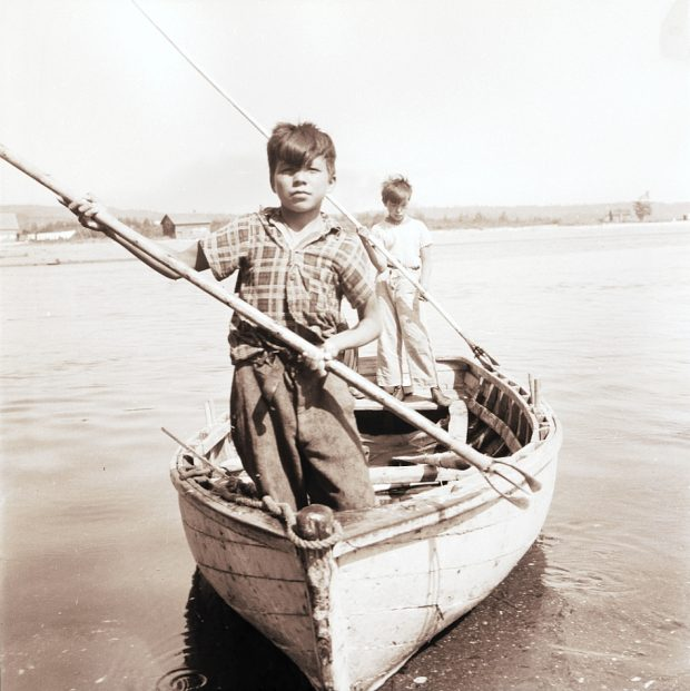 Two Aboriginal boys stand in a wooden rowboat near the shore, facing the photographer. Each one is holding a nigogue, a type of harpoon, above the water as if preparing to spear a fish. Black and white photograph.