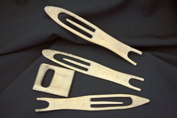 Four hand-crafted tools made of thin pieces of wood, lying on black fabric. They consist of three needles with a rounded point for knitting fishing nets and a small square object that serves as a mesh gauge.