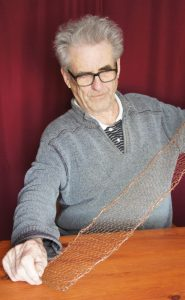 A man in his eighties sitting at a table holds a narrow strip of copper netting between his hands.