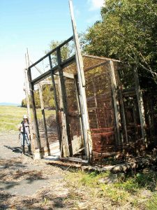 Trap made of wire mesh and wood plank framing. It measures about 6 m by 5 m and is beached in a cove bordered with trees. A man is standing on the left-hand side of the photograph. It's summertime.