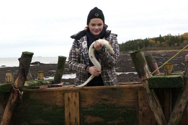 A teenage girl wearing a tuque and a coat stands in a wooden box used to hold eels captive in a weir. She is holding an eel in her hands. The river and a cove can be seen in the background.