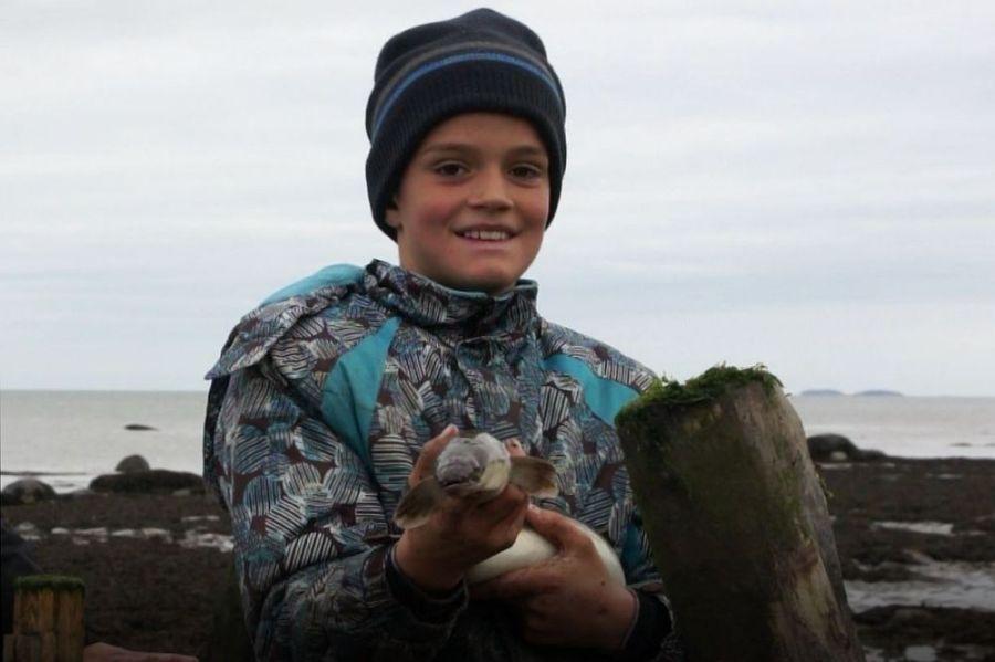 Un jeune garçon, en vêtements d'hiver et vu du torse jusqu'à la tête, tient fièrement une anguille dans ses mains. Il présente la tête du poisson et en arrière-plan on voit le fleuve.
