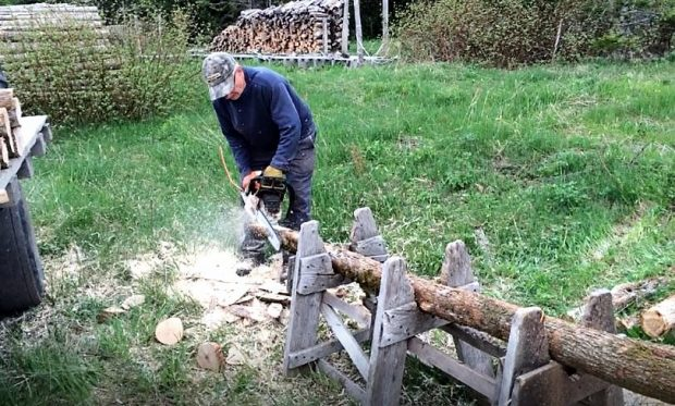 A man uses a chain saw to shape into a point the end of a post lying on a home-made sawbuck.