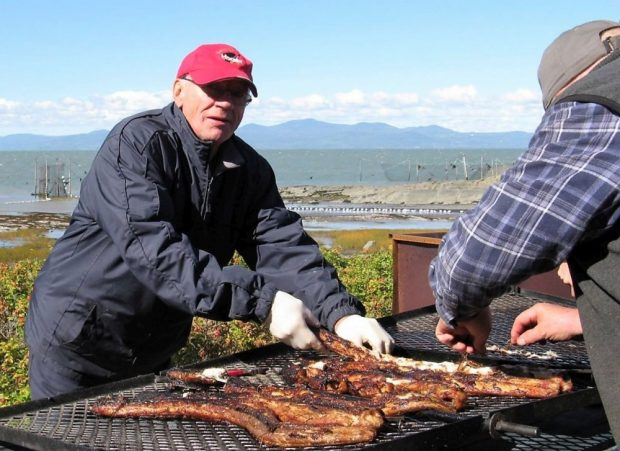 Two men grilling eel on a home-made barbecue next to the river.