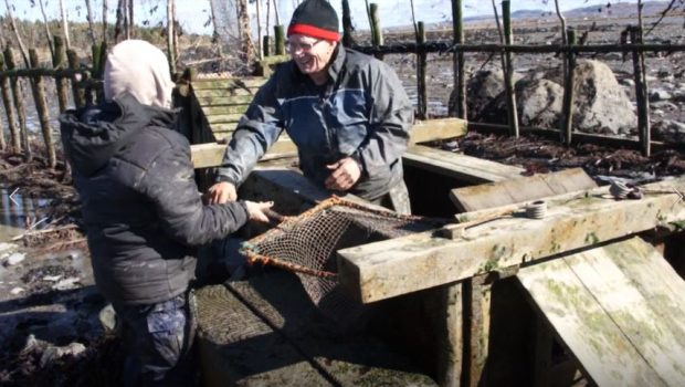 A man standing in a wooden box used to hold eels captive in the weir takes a net mounted on a square frame with a wooden handle from a woman who is handing it to him.