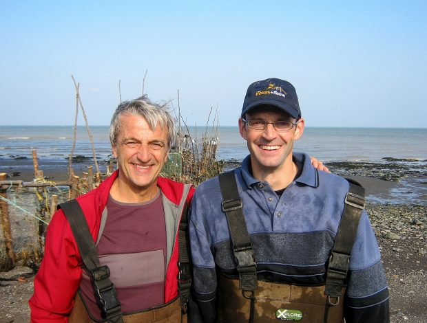 Head and shoulder view of two men returning from eel fishing, with their arms around each other's shoulders. An eel weir and the river can be seen in the background.