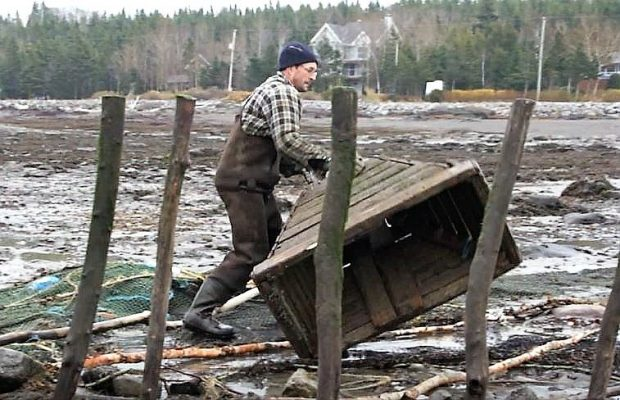 A man moves a large wooden funnel on the shore of the river by rolling it on the ground.