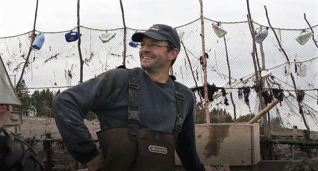 Head and shoulder view of a fisher with his right-hand on his hip, standing in front of the nets of his eel weir.