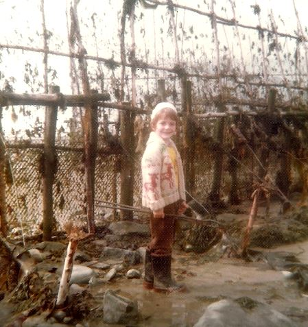In this photograph from the 1970s, a young boy wearing rubber boots, a jacket and a wool hat smiles as he poses in front of an eel weir with vertically installed fishing nets. He has his feet in the water.