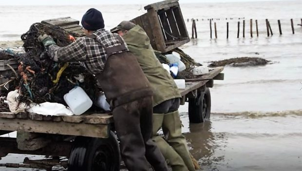 Two men in fishing clothes put a net on a trailer, whose wheels are sitting in the incoming tide.