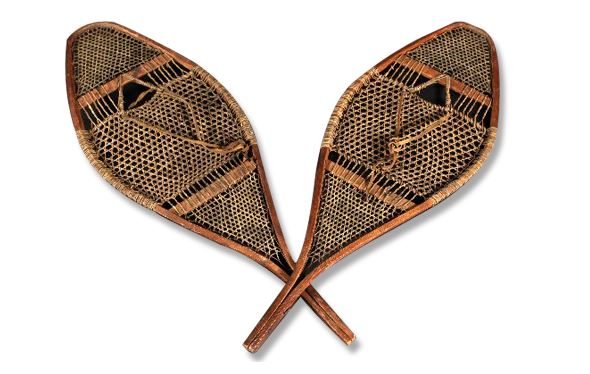 A pair of handcrafted snowshoes with a wooden frame and webbing made of babiche (strips of leather).