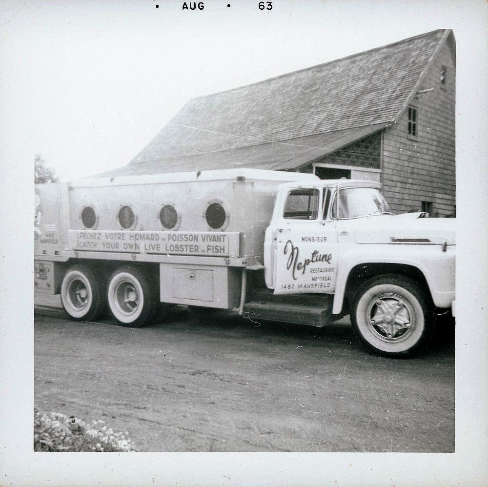 """Tank truck used for transporting live fish. A sign on the side of the truck says: """"Neptune Restaurant Montréal. Prenez votre homard et poisson vivant"""". Black and white photograph."""