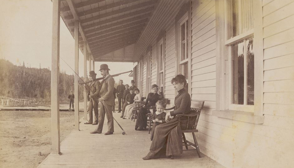 Sepia-toned photo of a group of people on the porch of the private club known as Laurentide House. The women and children are seated, while the men are standing with their fly- fishing rods. All are elegantly attired.