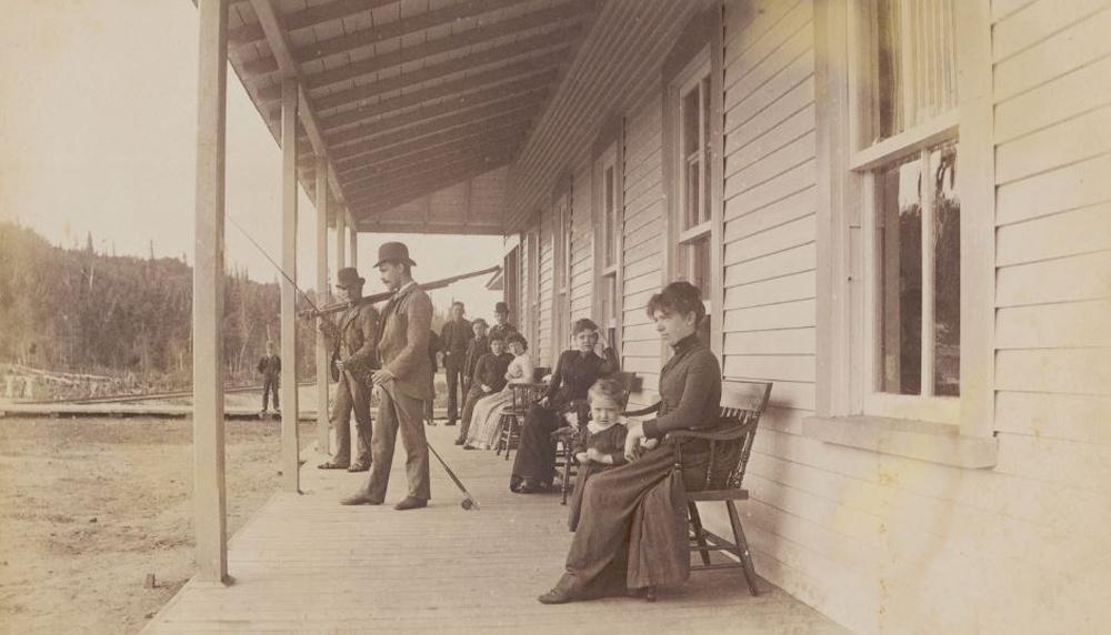 Photo en sépia, présentant des personnes sur le balcon du club privé Laurentide House.  Les femmes et les enfants étant assis et les hommes sont debout avec leur canne à moucher.  Tous sont très bien vêtus.
