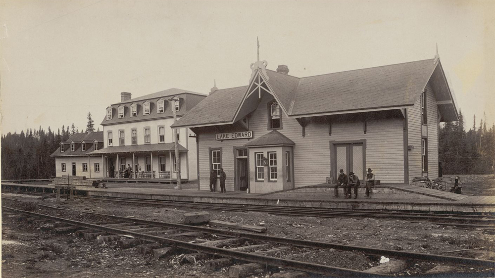 Sepia-toned photo of the Lac-Édouard train station; on the left stands lac Édouard's private club, Laurentide House.