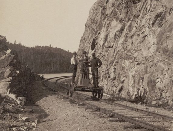 Sepia-toned photo of three men in a railway carriage and the rocky banks of lac Édouard. Inscription at bottom of photo reads: Rock cut Lake Edward.