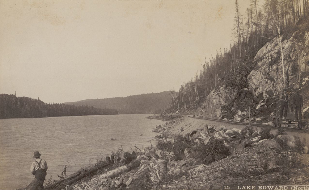 Sepia-toned photo shows how close the railroad is to lac Édouard. Workers on a railway carriage; in the foreground someone fishes on the banks of lac Édouard. Inscription at bottom of the photo reads: Lake Edward (North).