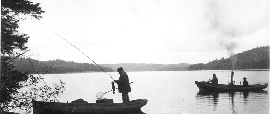 Black and white photo of fishermen in a steamboat on lac Édouard. In the foreground, a boat on the river's edge; in it stands a man unhooking a fish from his rod.
