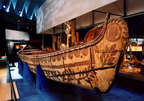 Photo en couleur, d'un canot de 36 pieds de long fabriqué en écorce de bouleau décoré avec des gravures.  Le canot est déposé sur un socle et est exposé dans au musée de la civilisation de Québec.