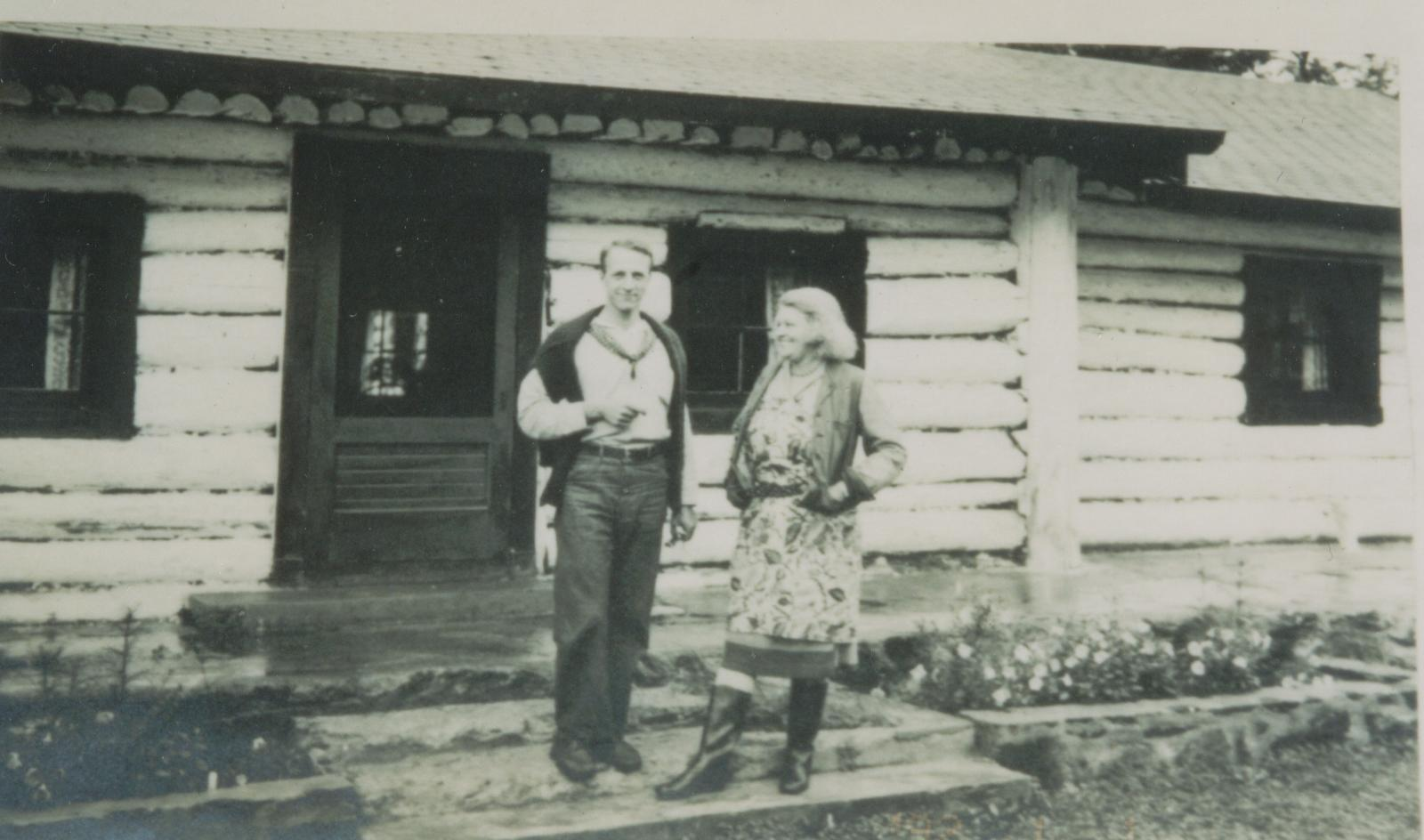 Black and white photo, A man, Fowler McCormick and a woman, Anne Stillman, stand in front of a log cabin.