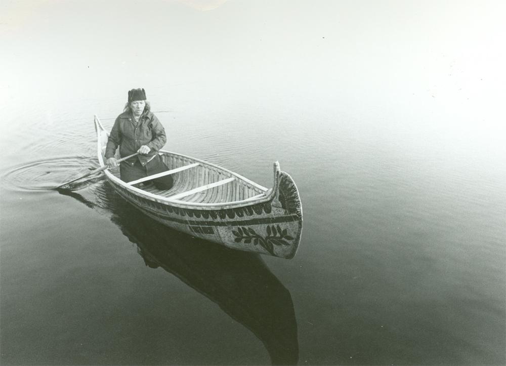 Photo of César Newashish in his birch bark canoe.