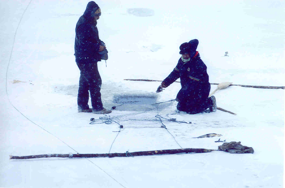 Color photo, two people are on a frozen lake. A hole is drilled in the ice and a fishing net is nearby. Two wooden poles will hold the net in place.