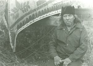 Black and white photo, César Newashish sitting next to a white birch bark canoe. Floral and ancestral motifs adorn the boat's hull.