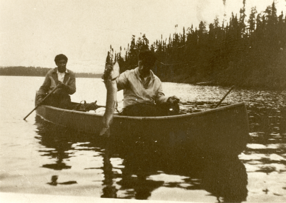 Sepia-toned photo, two men in a boat. The man seated near the front of the boat is holding a pike.