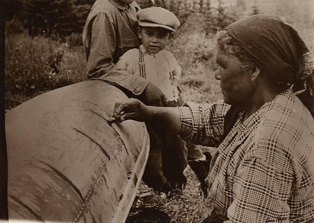 Photo sépia, en avant plan, une femme atikamekw applique de la gomme de sapin sur un canot en écorce de bouleau sous les yeux attentifs d'un jeune garçon