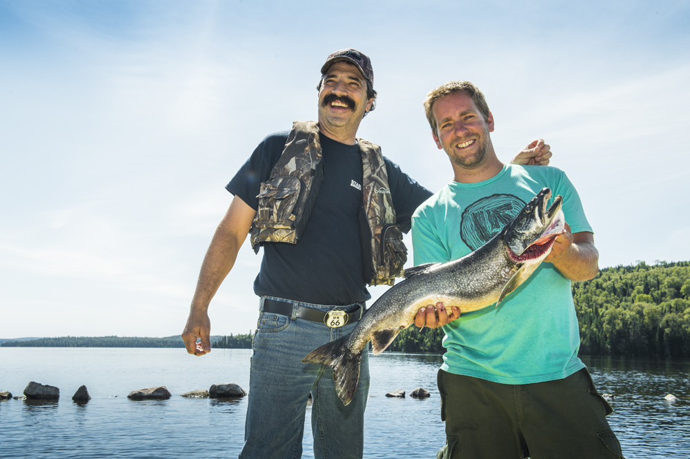 Colour photo, two men standing, holding a large grey trout; a lake can be seen in the background.