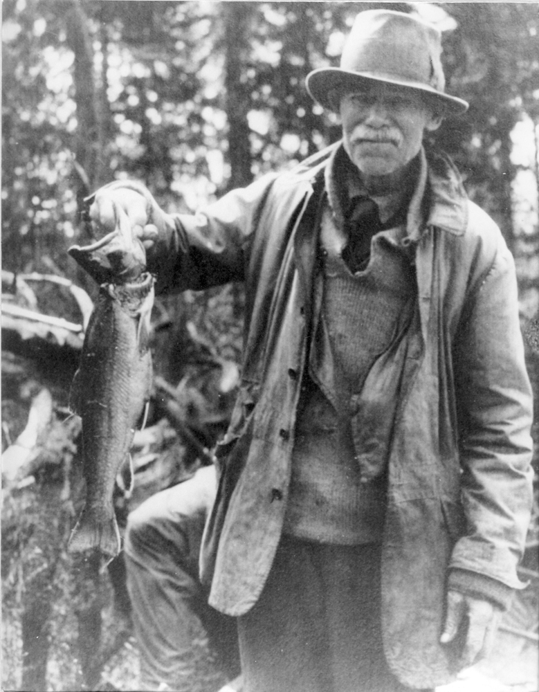 Black and white photo, a man standing, in his hands lies a beautiful speckled trout.