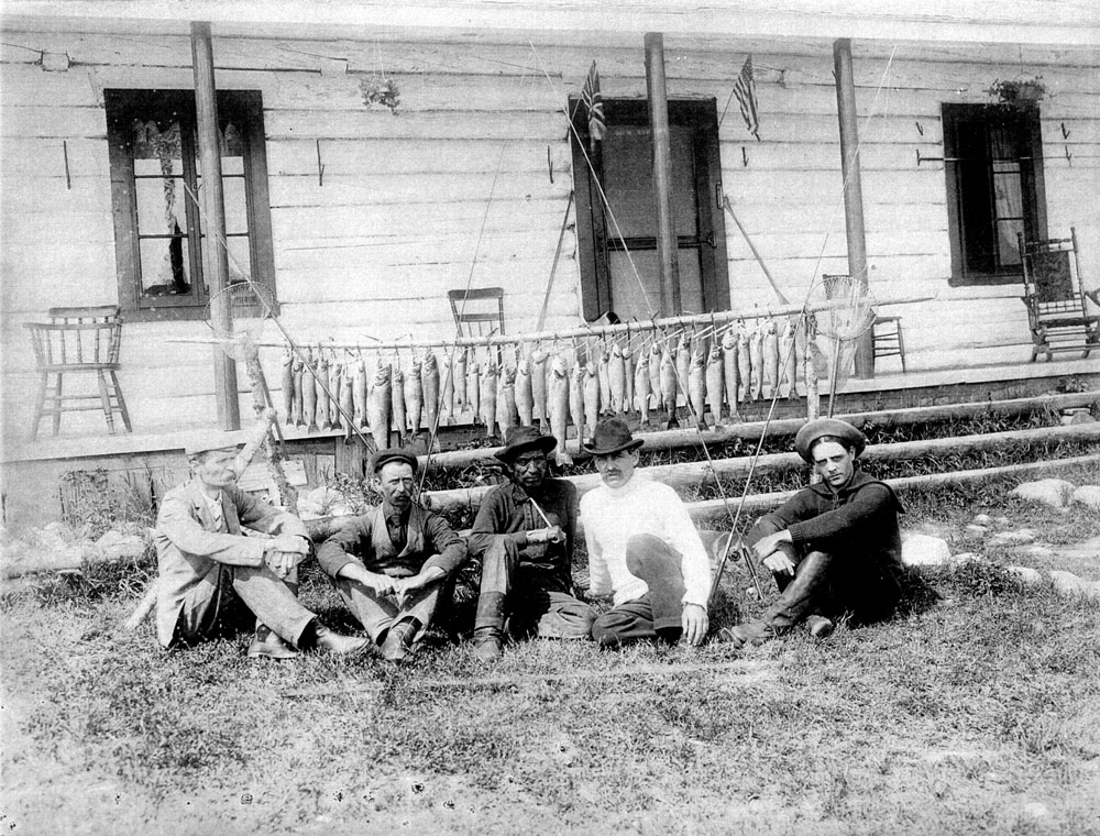 Black and white photo, a group of fishermen in front of the private club on lac Wayagamak, in the background several fish hang from a wooden pole.
