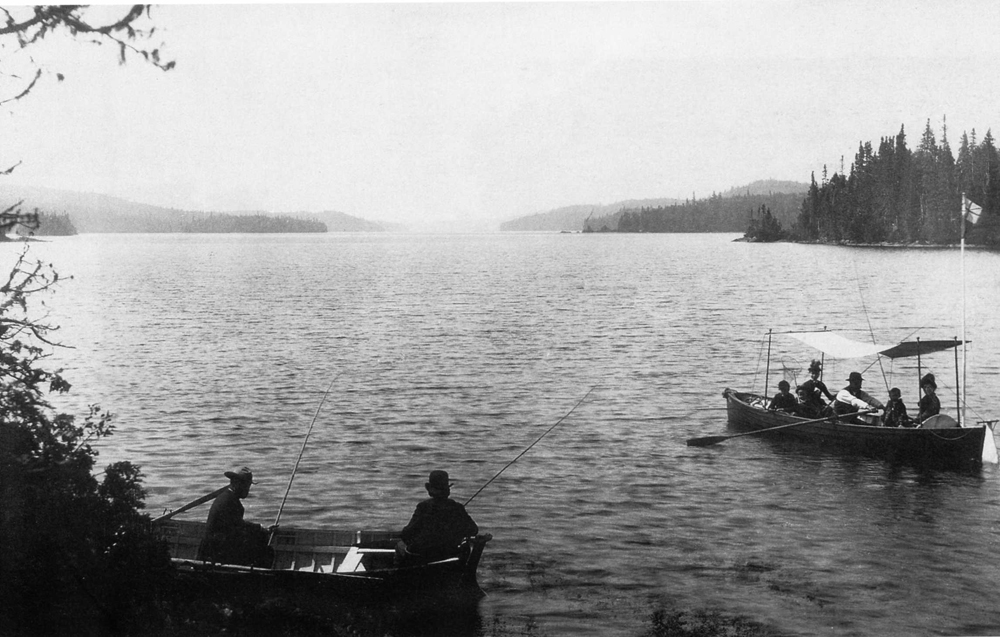 Black and white photo, two boats on sprawling lac Édouard. In the foreground, men fish in one boat, while further away women sit in the shade of a canopy built just for them.