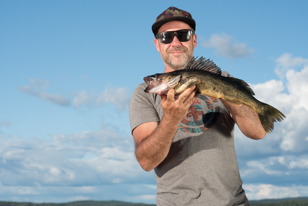 Colour photo, a man proudly holds a yellow walleye.