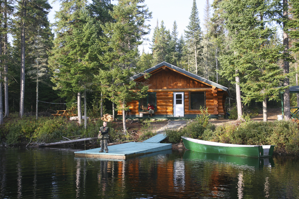 Colour photo, a log cabin with a lake just a few metres away. A child standing on the edge of a dock practices casting with a fly-fishing rod. A woman looks on from the balcony. Serene atmosphere, all is calm.