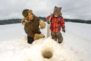 Colour photo, a father happy to initiate and his young son to ice fishing. A hole is drilled in the ice and a brimball is installed, they are ready for ice fishing.