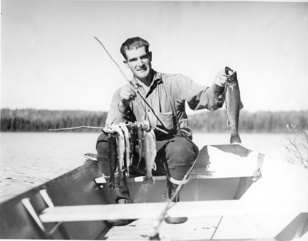 Photo en noir et blanc, un guide de pêche posant avec de belles truites mouchetées. Cet homme est assis dans une chaloupe.