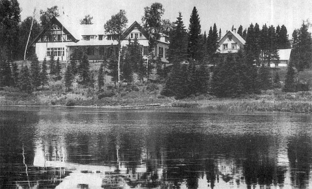 Black and white photo of a stylish house on the edge of a river. A smaller house on the right is partly hidden behind soaring spruce trees.
