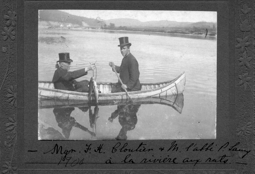 Black and white photo, two men in a birch bark canoe on a river.