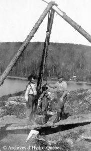 Photo en noir et blanc, trois travailleurs. Trois billots reliés ensemble supportant une poulie aidant à puiser l'eau potable.
