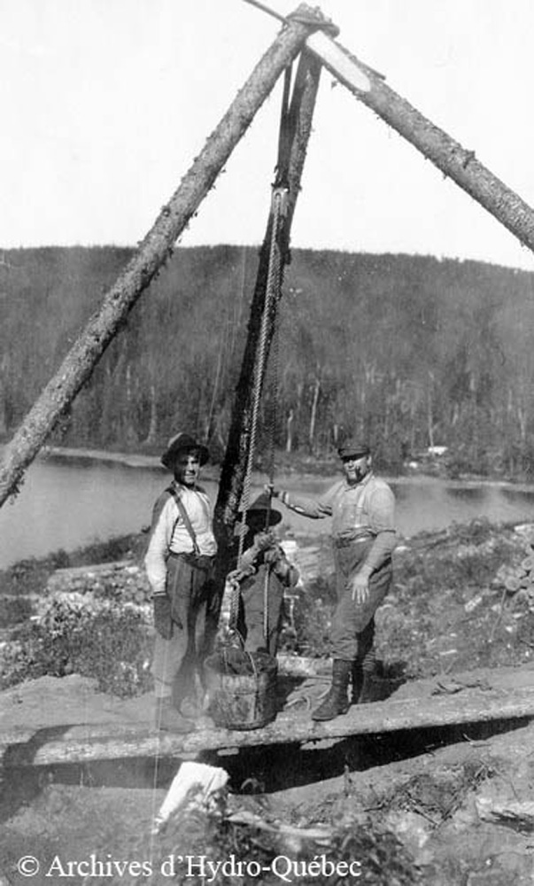 Black and white photo, three workers. Three logs bound together support a pulley that helps retrieve clean drinking water.
