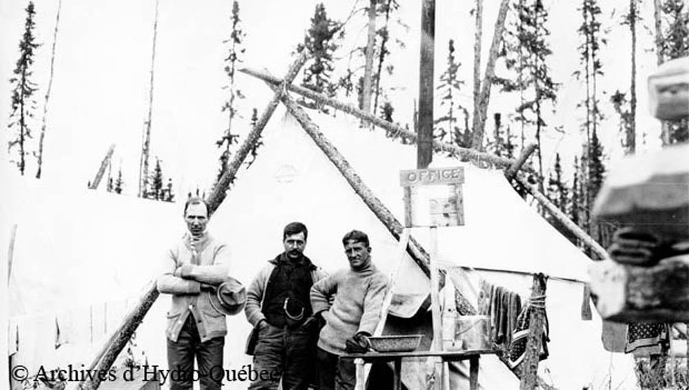 Black and white photo, three workers in front of a prospector camp. Canvas tent with wooden logs as its structure. In front of the tent, a wooden sign with the word Office.
