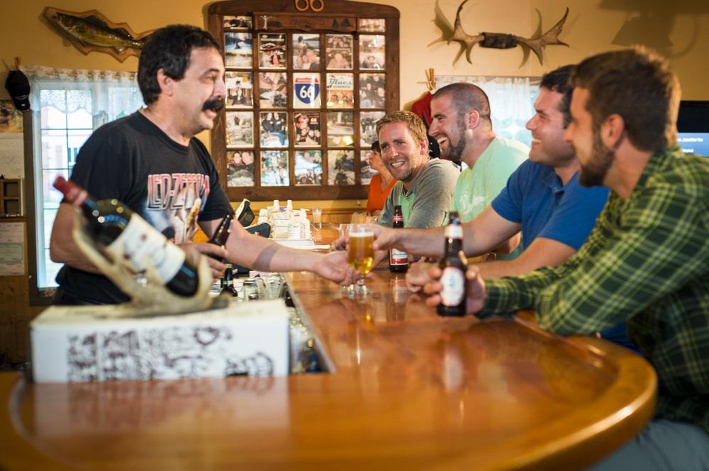Photo couleur, 4 hommes assis à un comptoir prenant une bière.