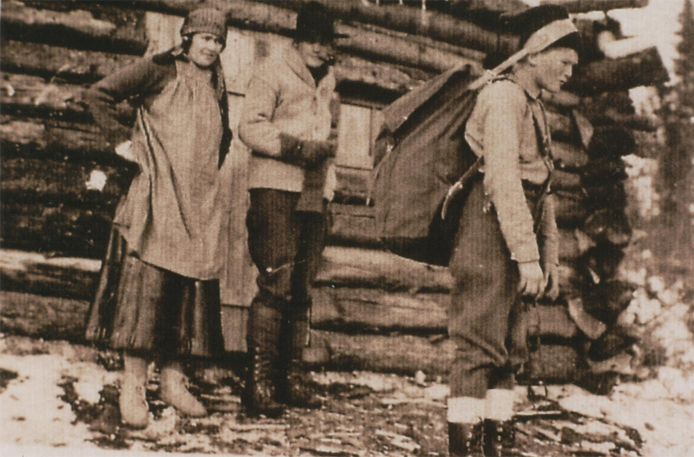 Sepia-toned photo, a man, woman and child stand in front of a log cabin, a thin layer of snow covers the ground. The child, getting ready to leave, wears a large backpack equipped with a leather strap to help with the portage.