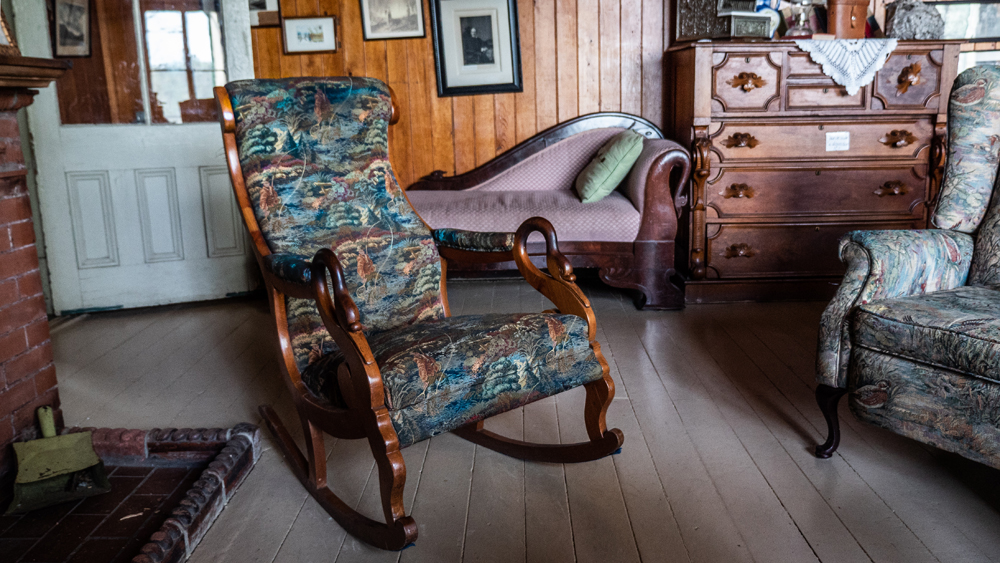 Colour photo of a rocking chair next to a fireplace. The chair's armrests taper off into the shape of a swan, and the upholstery is embellished with a hunting motif.